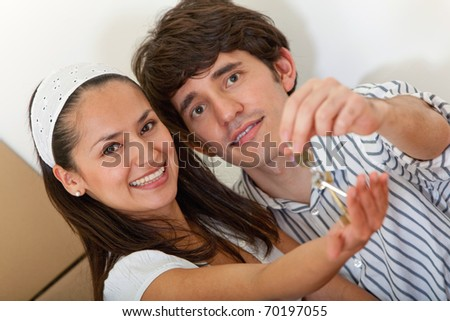 Loving couple holding keys to a new house while moving