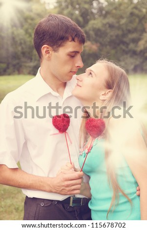 Loving couple holding red heart on a stick - stock photo