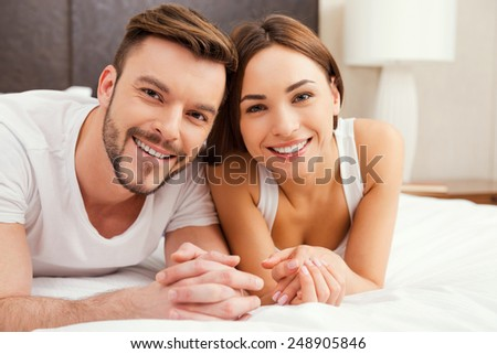 Loving couple in bed. Beautiful young loving couple lying in bed together and smiling - stock photo