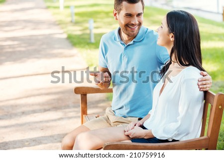 Loving couple in park. Side view of cheerful young loving couple sitting on the bench together and talking  - stock photo