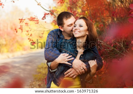 Loving couple in the autumn garden. Man and woman are embracing through the red leaves. - stock photo