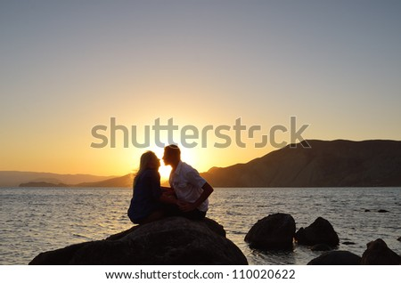 Loving couple kissing at the sea in the evening