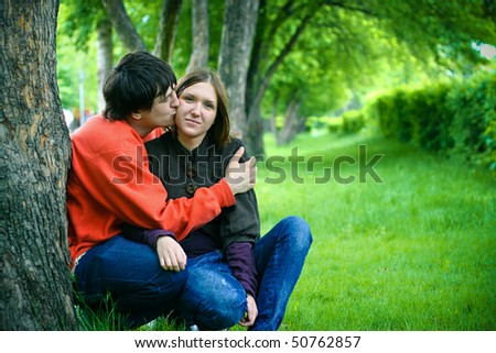 loving couple kissing under a tree in park - stock photo