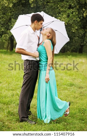 Loving couple kissing under a white umbrella - stock photo