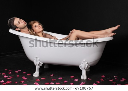 Loving couple lie in a bathroom on a black background