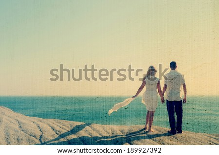 Loving couple looking at the sea holding hands. Filtered image: vintage, grunge and texture effects - stock photo