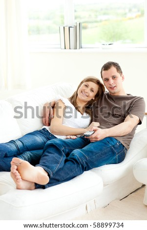 Loving couple lying on the sofa smiling at the camera in the living room