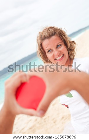 Loving couple on beach, red heart in hand - stock photo