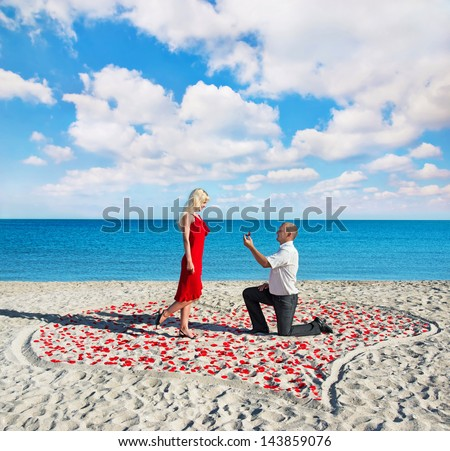 Loving couple on sea sandy beach - a man making proposal with gold ring  to his pretty blonde woman in red dress in the heart of roses petals - stock photo