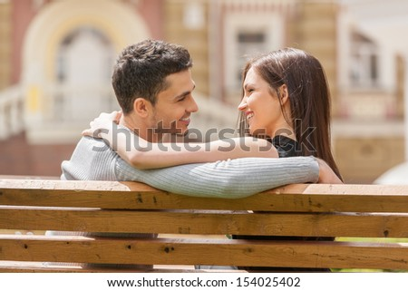 Loving couple on the bench. Rear view of cheerful young couple sitting close to each other on the bench and smiling