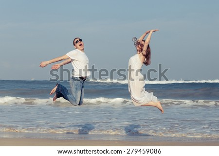 Loving couple running on the beach at the day time. Concept of friendly family. - stock photo