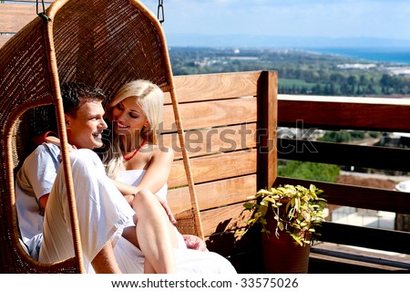 Loving couple sitting on swing with pasture view - stock photo