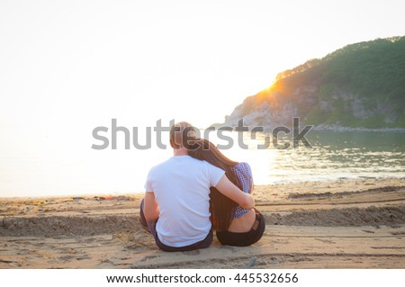 Loving couple sitting on the sandy beach. Romantic couple meets sunset on the ocean. Relations. Happiness. - stock photo