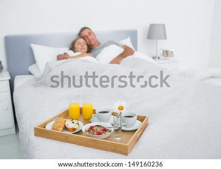 Loving couple sleeping with breakfast tray on bed at home in bedroom