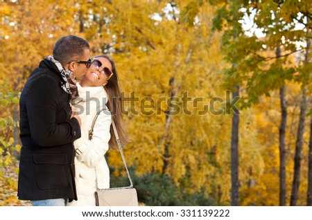 Loving couple smiling and enjoying the autumn season, man kissing woman. Holidays, love, travel, tourism, relationship and dating concept - romantic couple in the autumn park. - stock photo
