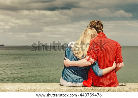 Loving couple spending leisure time together at beach sitting on sea shore with red heart hugging rear view