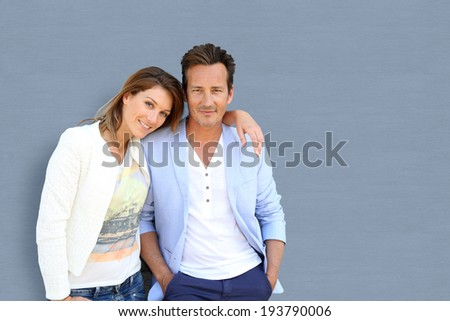 Loving couple standing on grey background - stock photo