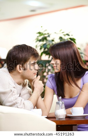 Loving couple talks behind a little table in cafe