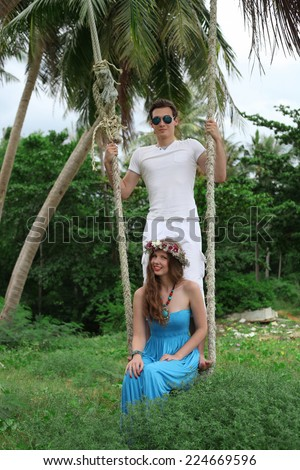 Loving couple. The guy and the girl on a swing.  - stock photo