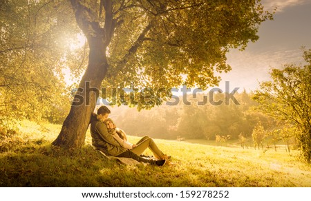 Loving couple under a big tree in the park in autumn - stock photo