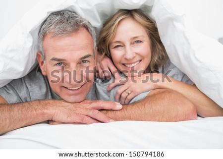 Loving couple under the duvet smiling at camera in bedroom at home