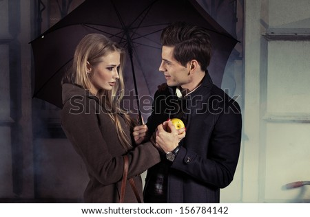 Loving couple under umbrella - stock photo