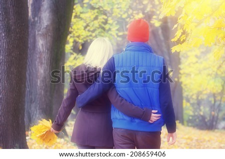 Loving couple walking arm in arm in a beautiful autumn park. Soft effect. Color toning - stock photo
