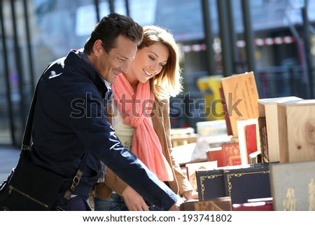 Loving couple walking by book fair on week-end - stock photo