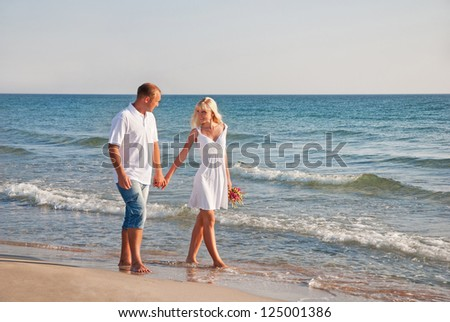 loving couple walking on the sea beach at summer
