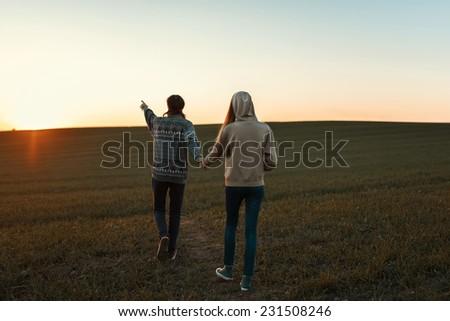 Loving couple walking towards the sunset on the field - stock photo