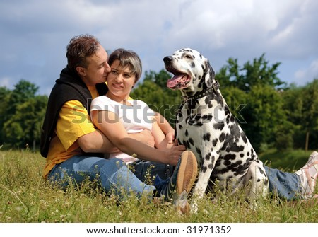 loving couple with a Dalmatian outdoors - stock photo