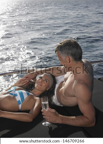 Loving couple with champagne flute relaxing at the edge of yacht by sea - stock photo