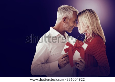 Loving couple with gift on dark background - stock photo