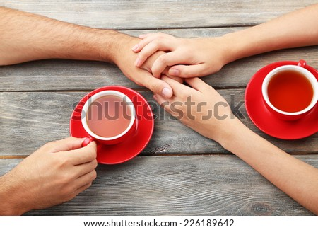 Loving couple with hot drinks on table - stock photo