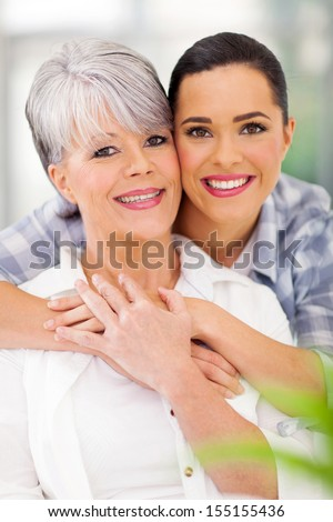 loving daughter hugging middle aged mother at home