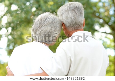 loving elder couple on a walk in a summer park - stock photo