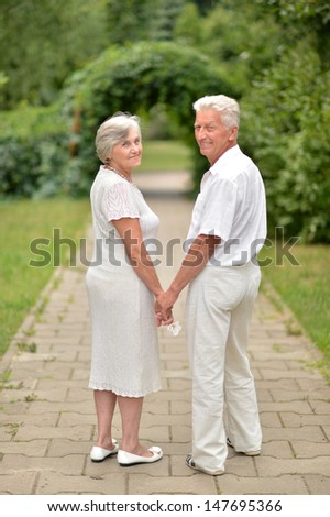 loving elderly couple on a walk in the park together - stock photo