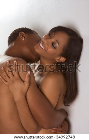 Loving ethnic black African-American young affectionate nude heterosexual couple in affectionate sensual kiss. - stock photo