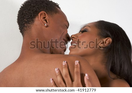 Loving ethnic black African-American young affectionate nude heterosexual couple in affectionate sensual kiss - stock photo