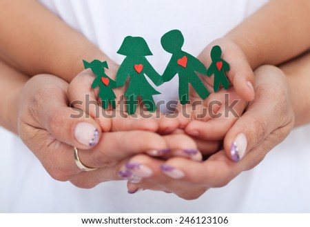 Loving family concept with adult and child hands holding paper people- shallow depth of field - stock photo