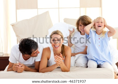 Loving family having fun together in the bedroom - stock photo