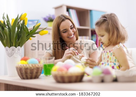 Loving family in easter holiday painting eggs  - stock photo