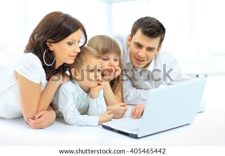 Loving family looking at a laptop lying down on bed at home - stock photo