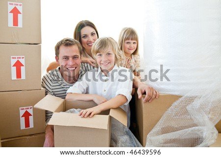 Loving family packing boxes while moving house - stock photo