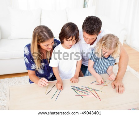 Loving family playing mikado in the living room at home - stock photo