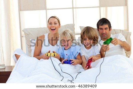Loving family playing video game lying on bed - stock photo