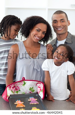 Loving family showing handmade cookies in the kitchen - stock photo