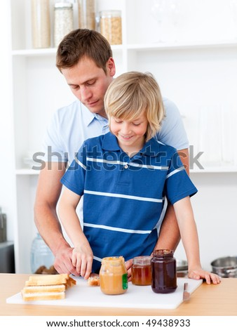 Loving father helping his son prepare the breakfast in the kitchen - stock photo