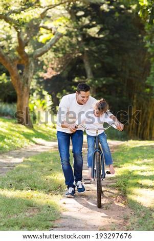 loving father teaching daughter to ride bike  - stock photo