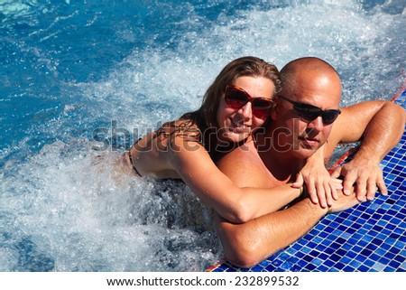 Loving happy couple in hot-tub. Summer vacation. - stock photo